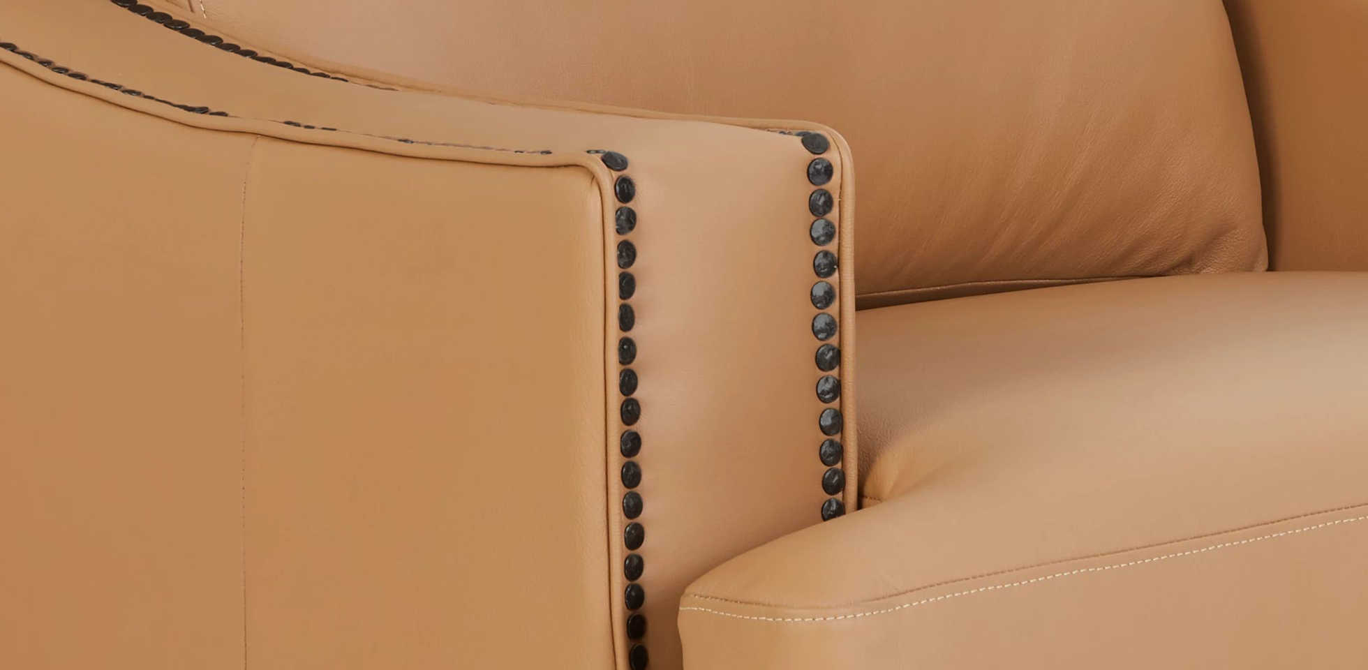 Closeup of nailhead trim on the arm of a Makenna duo® Reclining Sofa