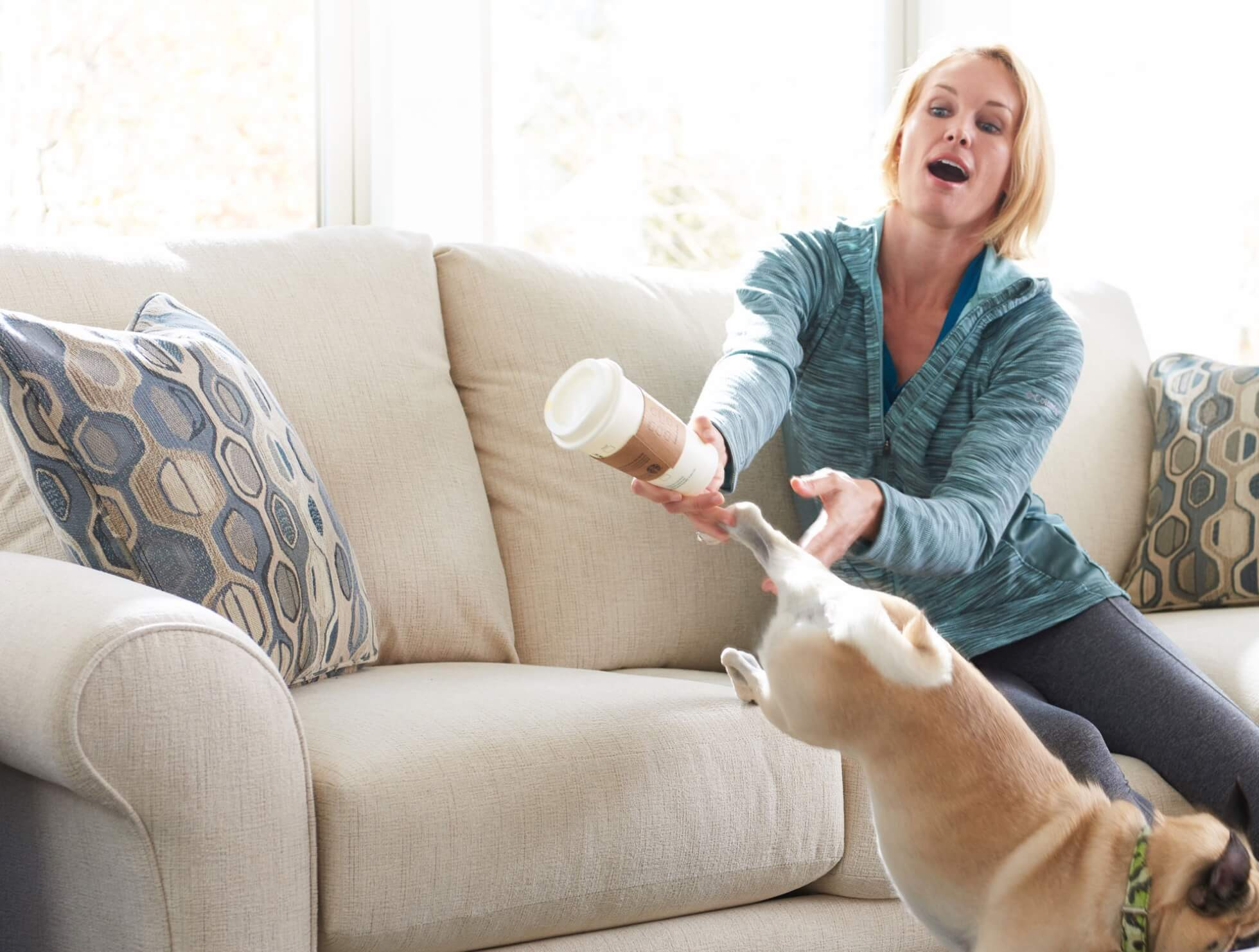 Lady dropping coffee on sofa