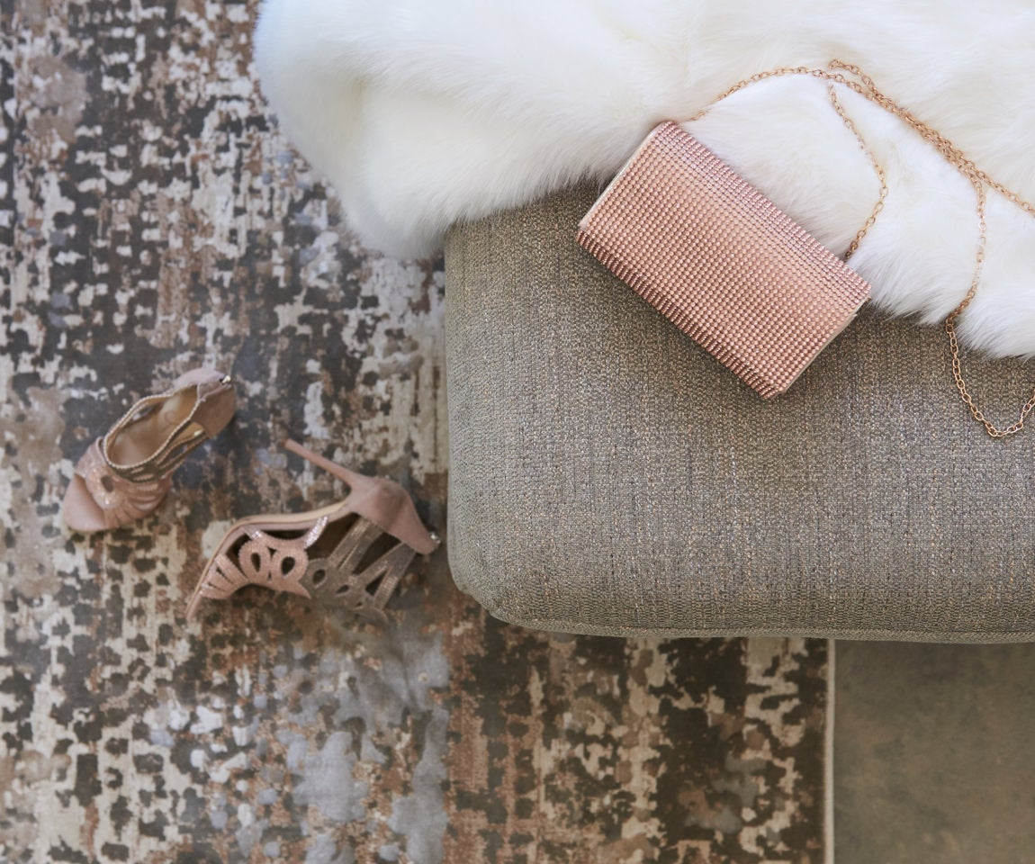 Closeup of Tribeca Sectional with faux fur throw, sparkly purse and tan heels
