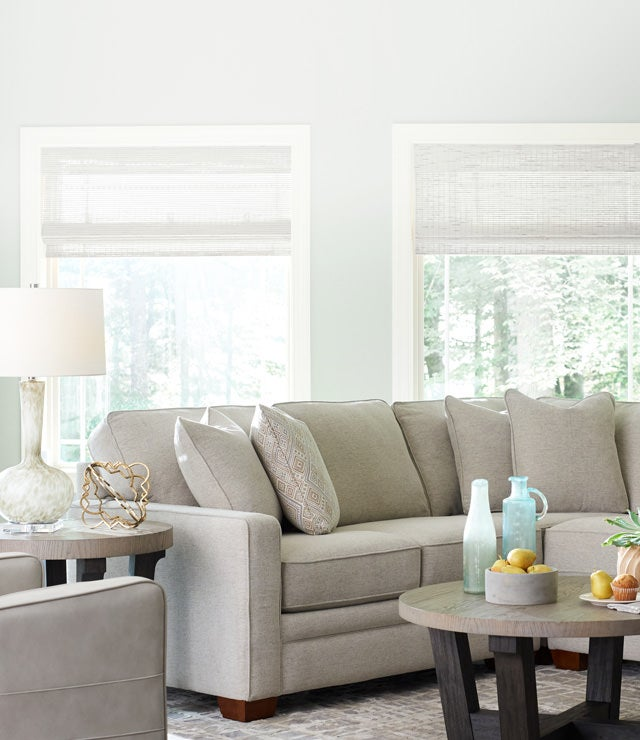 Home-Decor room scene with Midtown Swivel Glider, Meyer Sectional, Beckham Round Cocktail Table and accessories