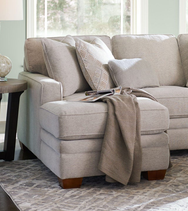 Room scene of Meyer Sectional with book and a throw on top