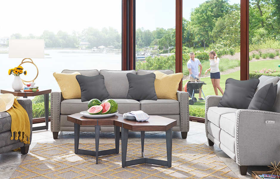 Summer living room scene with Makenna duo® Reclining Sofa, Loveseat and Chair and accessories in natural materials