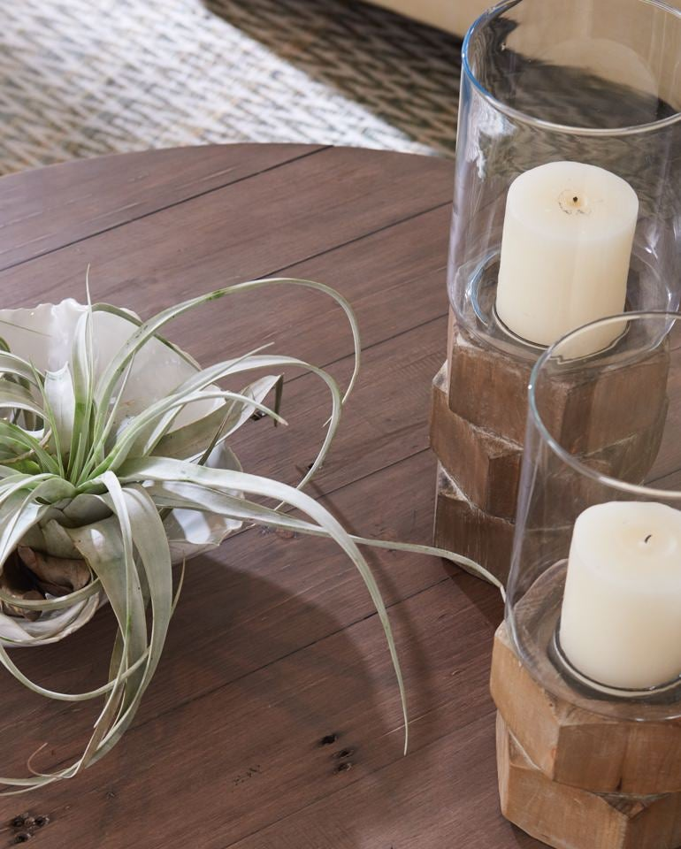 Closeup of Reclamation Place Trestle Round Cocktail Table with plant and candles