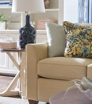 Closeup of Dixie Queen Sleep Sofa and Reclamation Place Trestle Round End Table with accessories