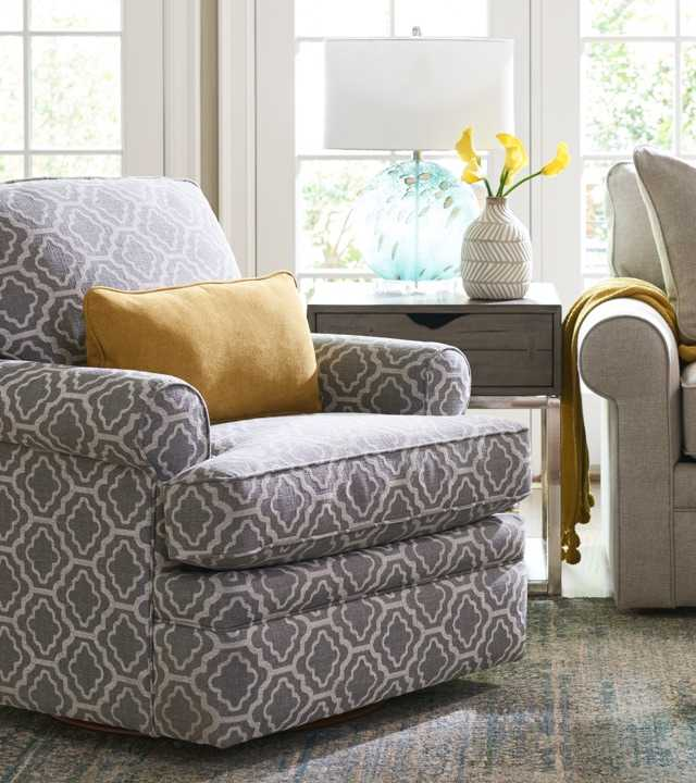 Comfortably Casual Room scene with Roxie Swivel Chair, area rug and accessories