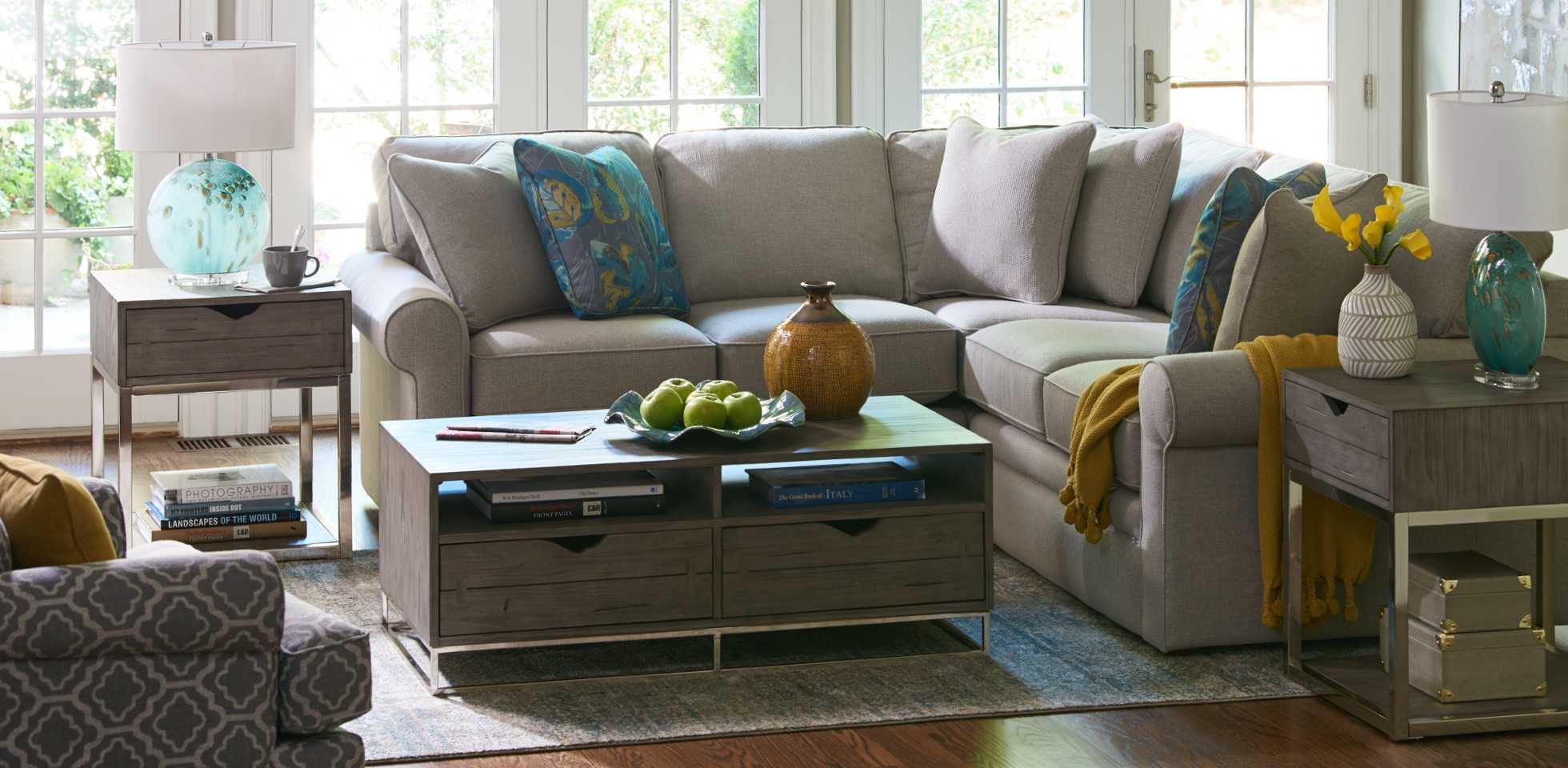 Comfortably Casual room scene with Collins Sectional, Roxie Swivel Chair and junction-truss-cocktail-table with area rugs and accessories
